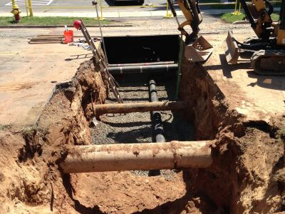 heavy equipment being used to excavate and expose underground piping