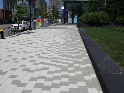 A wide sidewalk paved with different shades of concrete tiles arranged in a design.