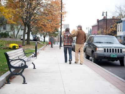 A wide sidewalk with benches facing the sidewalk, backs against a greenspace. Parked cars on the road and pedestrians walking along the sidewalk.