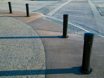 An intersection with bollards arranged with space to get to the curb, and urban braille at the entrance tothe crosswalk. The paving in teh crosswalk has a line of differen material on either side instead of painted lines.