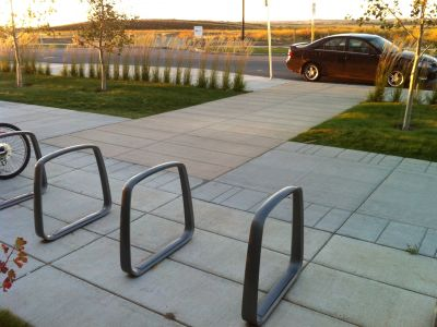 Simple bike racks on a wide sidewalk.