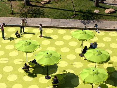 Painted pavement with green polka dots, with matching green umbrellas & folding chairs