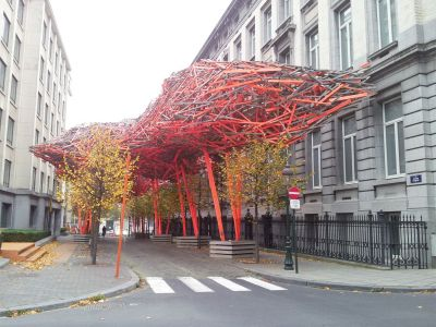 Tree-like sculptures coming out of tree wells on a sidewalk