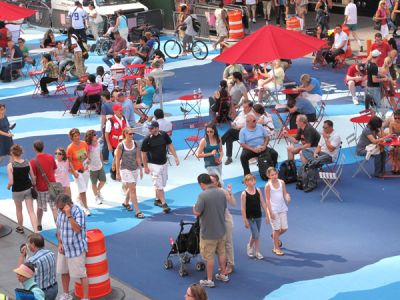 Painted pavement for a temporary pop up plaza. People walking, sitting on folding chairs, under umbrellas.