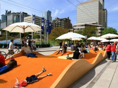 Artistic orange street furniture that looks like a wave. People sitting, a child lying down, umbrellas.