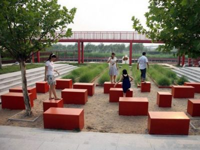 Red cubes as furniture in a public space. People standing on the cubes.
