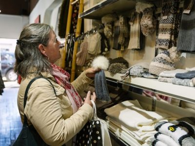A customer at a store. Looking at winter hats, gloves & scarves.