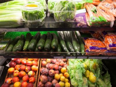 A grocery store produce aisle. Includes carrots, cucumber & lettuce.