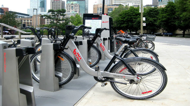 row of grey bikes at a docking station