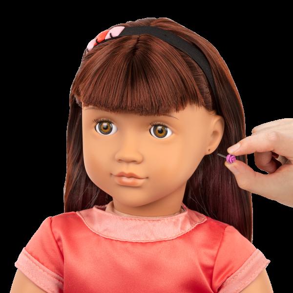 Detail of Adelita having earrings put on
