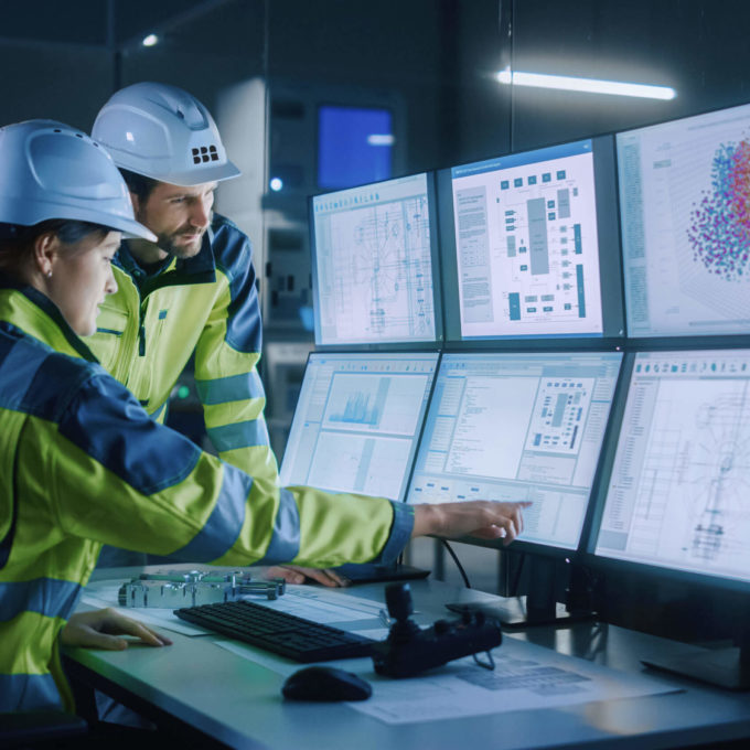 Automation and Industrial Technologies (IT/OT) - Two people looking at screens in a control room