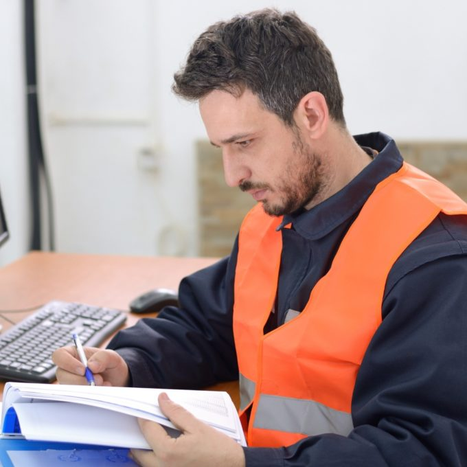 Industrial Control Systems  - Man taking notes in front of computer