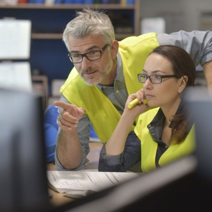 Two people looking at a computer screen - One is pointing at the screen