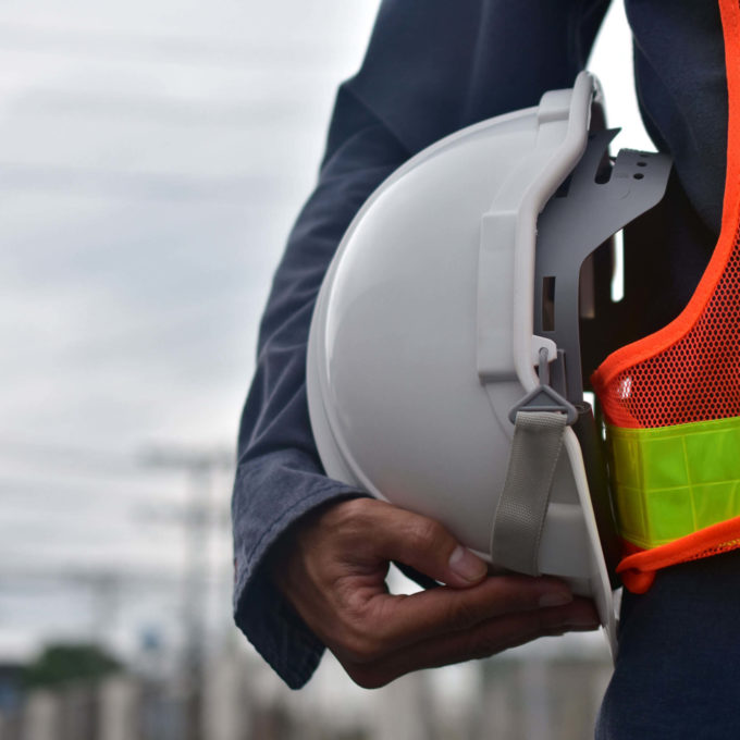 Health and safety - Person holding helmet