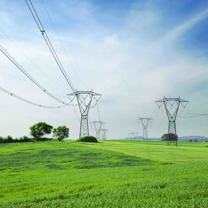 Power Transmission and Distribution - Pylons with green grass and blue sky