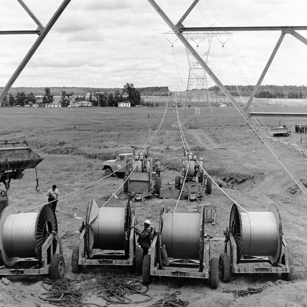 <p>Workers unrolling four conductors on a line, 1964.</p> <p>©Hydro-Québec archives.</p><p> </p>