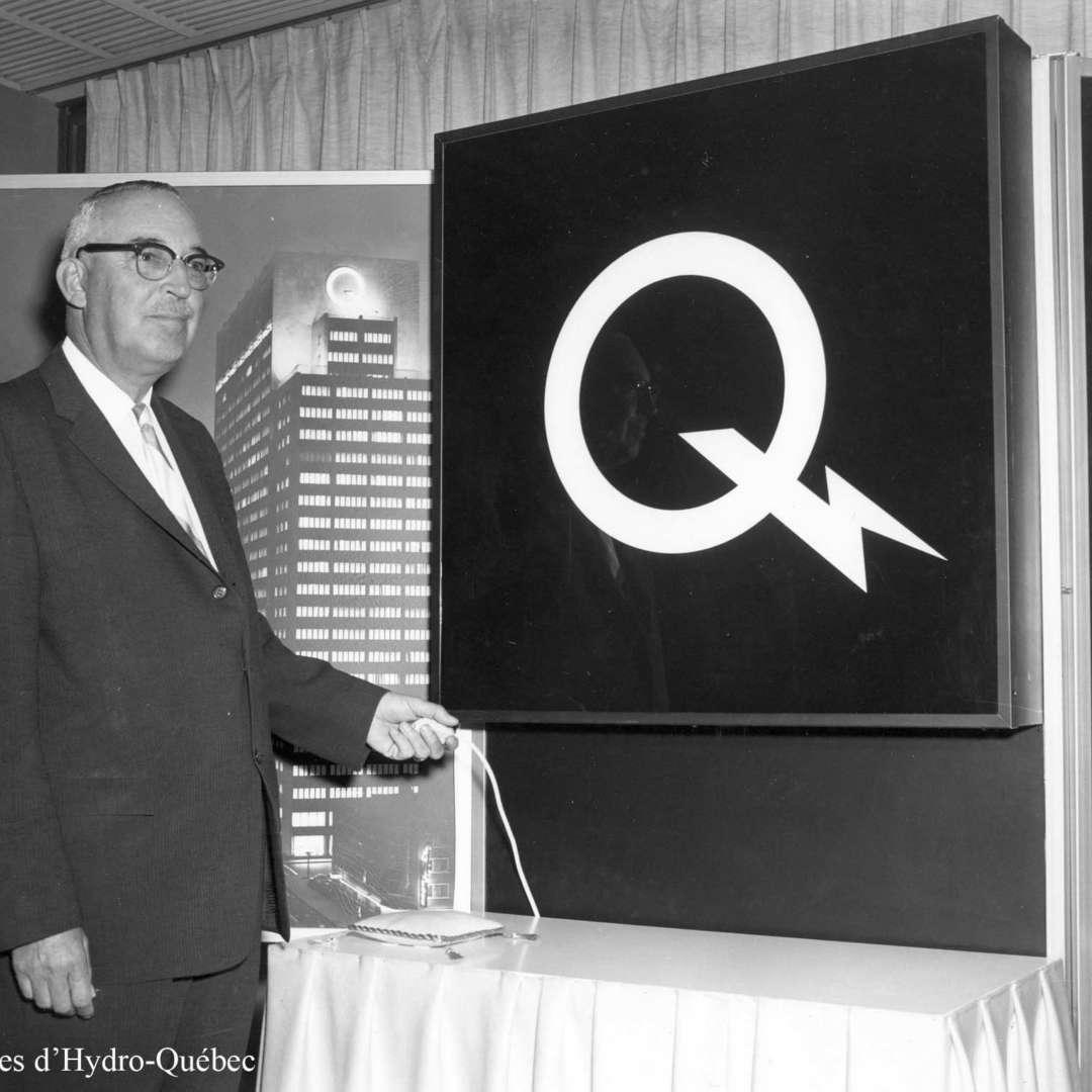 <p>Dévoilement par le président d'Hydro‑Québec Jean‑Claude Lessard du nouveau logo de l'entreprise, symbole d'une ère nouvelle pour la société d'État, 1965</p> <p>©Archives d'Hydro‑Québec</p>