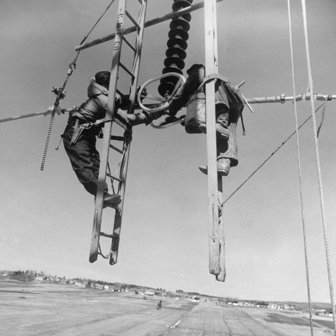 <p>Suspension d'un câble au moyen d'isolateurs par deux monteurs intrépides – première ligne à 315kV, 1956</p> <p>©Archives d'Hydro‑Québec</p>