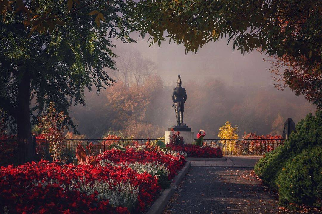Winning photo from the 2019 Instagram contest taken at Major's Hill Park. It shows a flowerbed with red flowers and the statue of Colonel John-By on a misty autumn background.