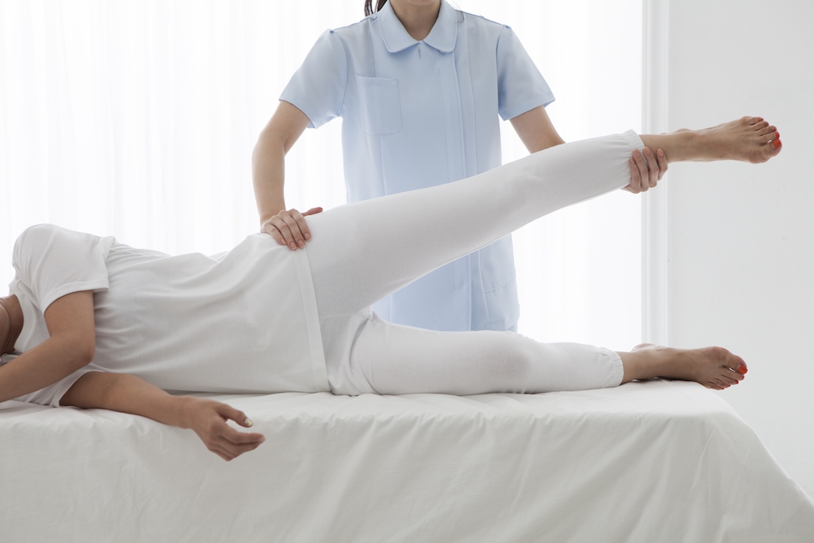 physiotherapist assisting patient with side-lying leg raise