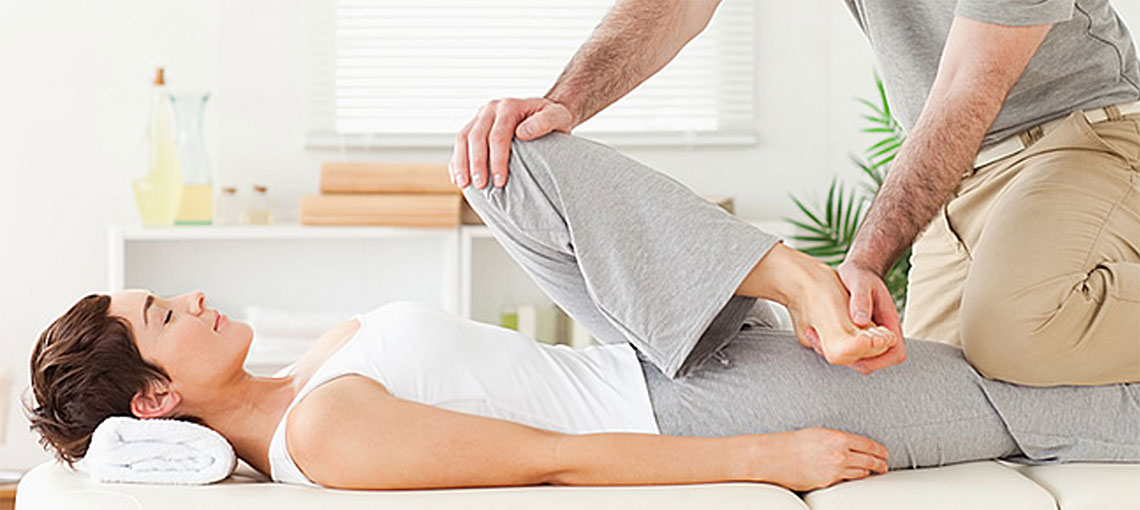 therapist stretching female patient's hip