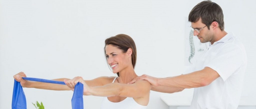 physiotherapist assisting female patient with resistance band shoulder exercise