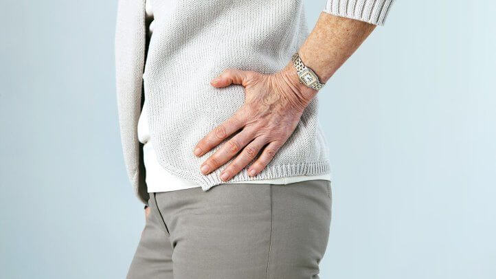 woman holding hip due to pain