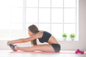 young athletic woman stretching hamstrings in long sitting