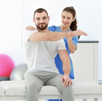 female physiotherapist assisting male patient with shoulder exercise