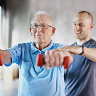 physiotherapist assisting an elderly patient with dumbbell shoulder raises