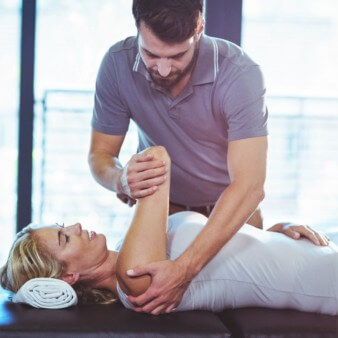 male physiotherapist mobilizing a female patient's shoulder