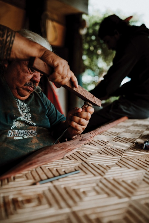 Alex King, Michael Tavioni carving a spear for a buyer, 2019. Courtesy of the artist.