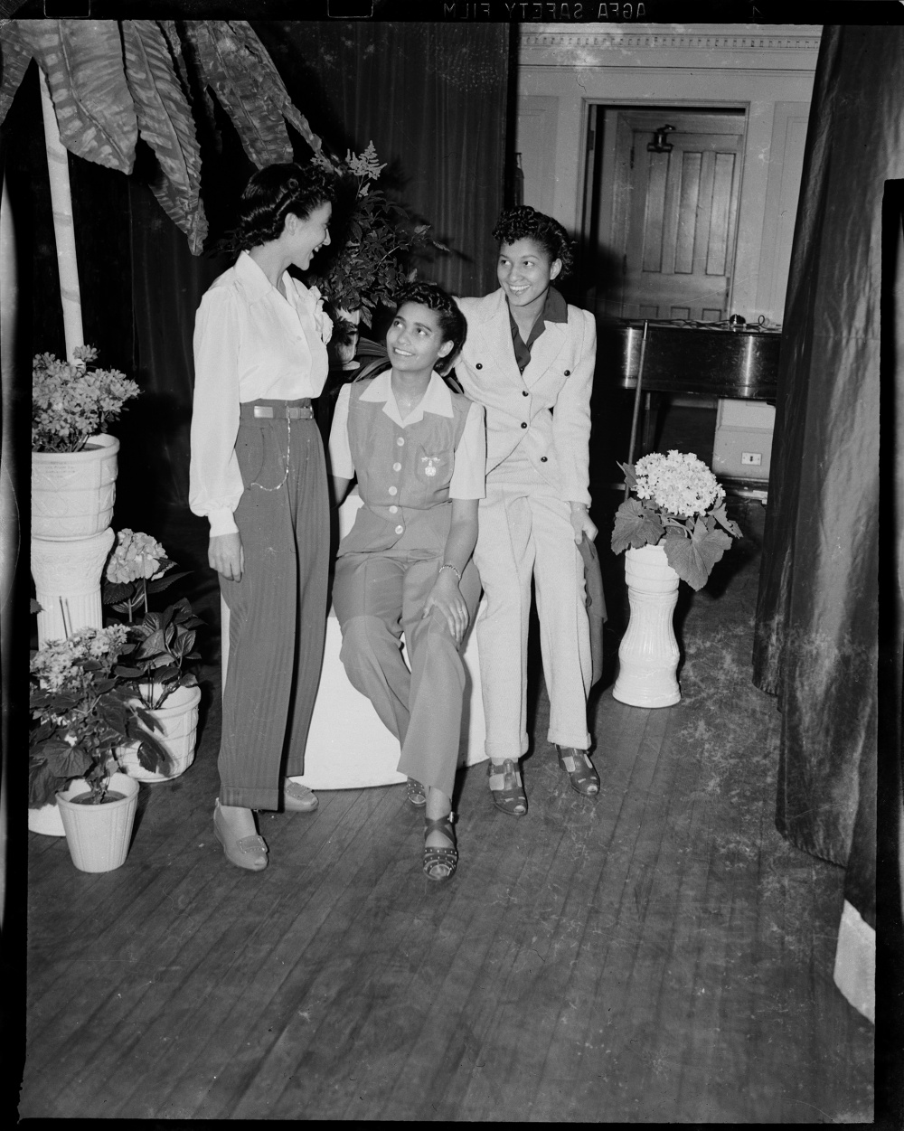 """Charles """"Teenie"""" Harris, Three women wearing pants, pictured at the Beauty Shop Owners' Fashion Review in Schenley High School, 1945. Silver Gelatin print. Courtesy of Carnegie Museum of Art, Pittsburgh."""