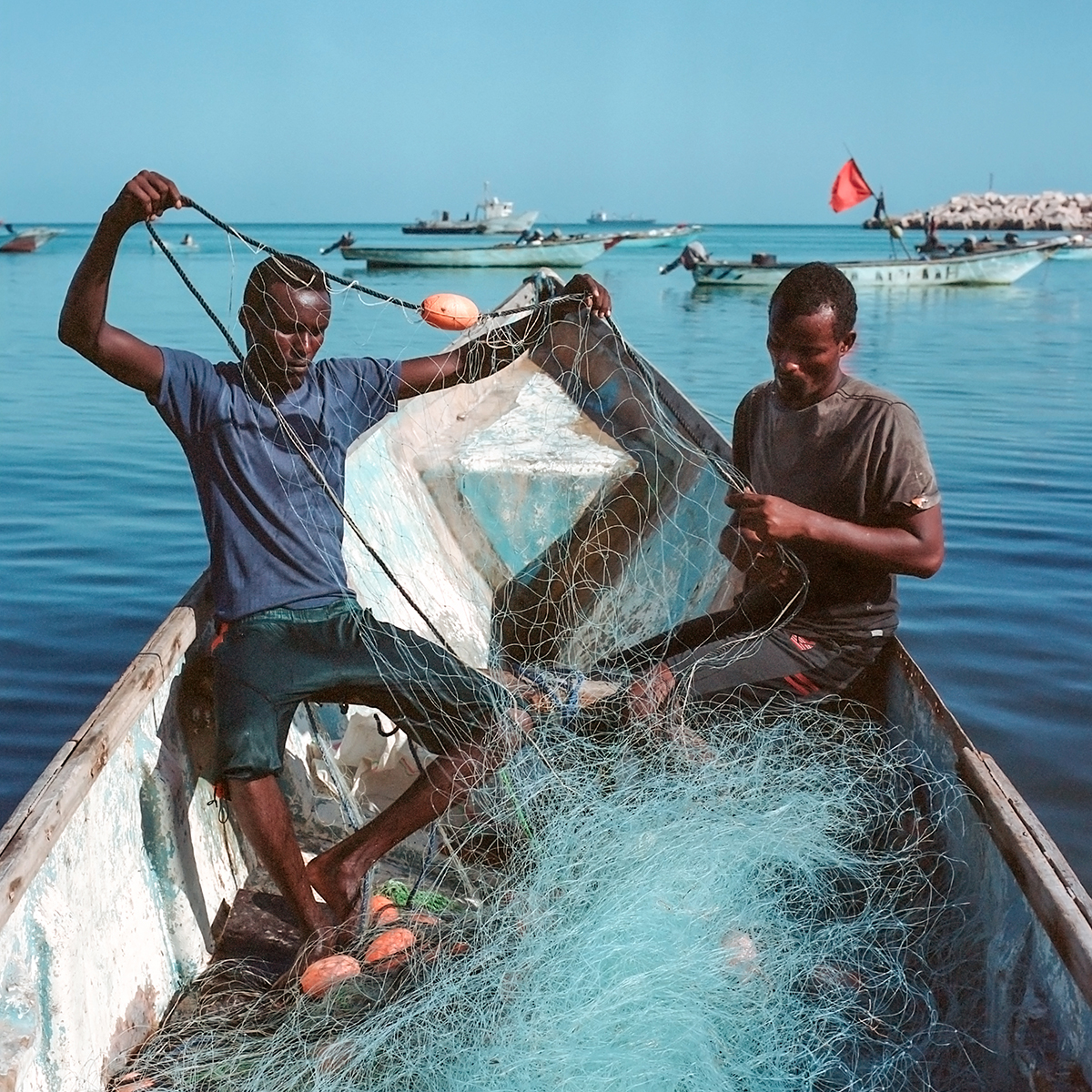 """Nichole Sobecki, Ahmed and Hamza untangle their nets, May 2016. Archival pigment print, 20 × 20""""."""