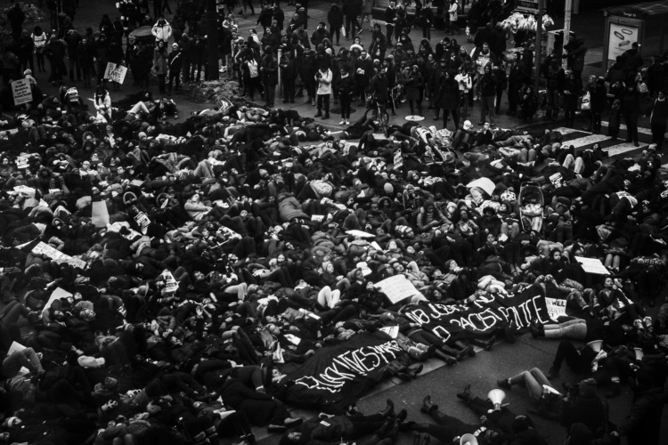 """Jalani Morgan, Black Lives They Matter Here (The power of symbolism: protesters perform a 'die-in' by laying on the ground at Yonge and Dundas Square in Toronto. This was in soli- darity and in rage of the decision of the New York grand jury to not indict the police officers responsible for the murder of Eric Garner), Toronto, Canada., 2014. Inkjet print on vinyl, 8.7x6.5"""". Courtesy of the artist."""