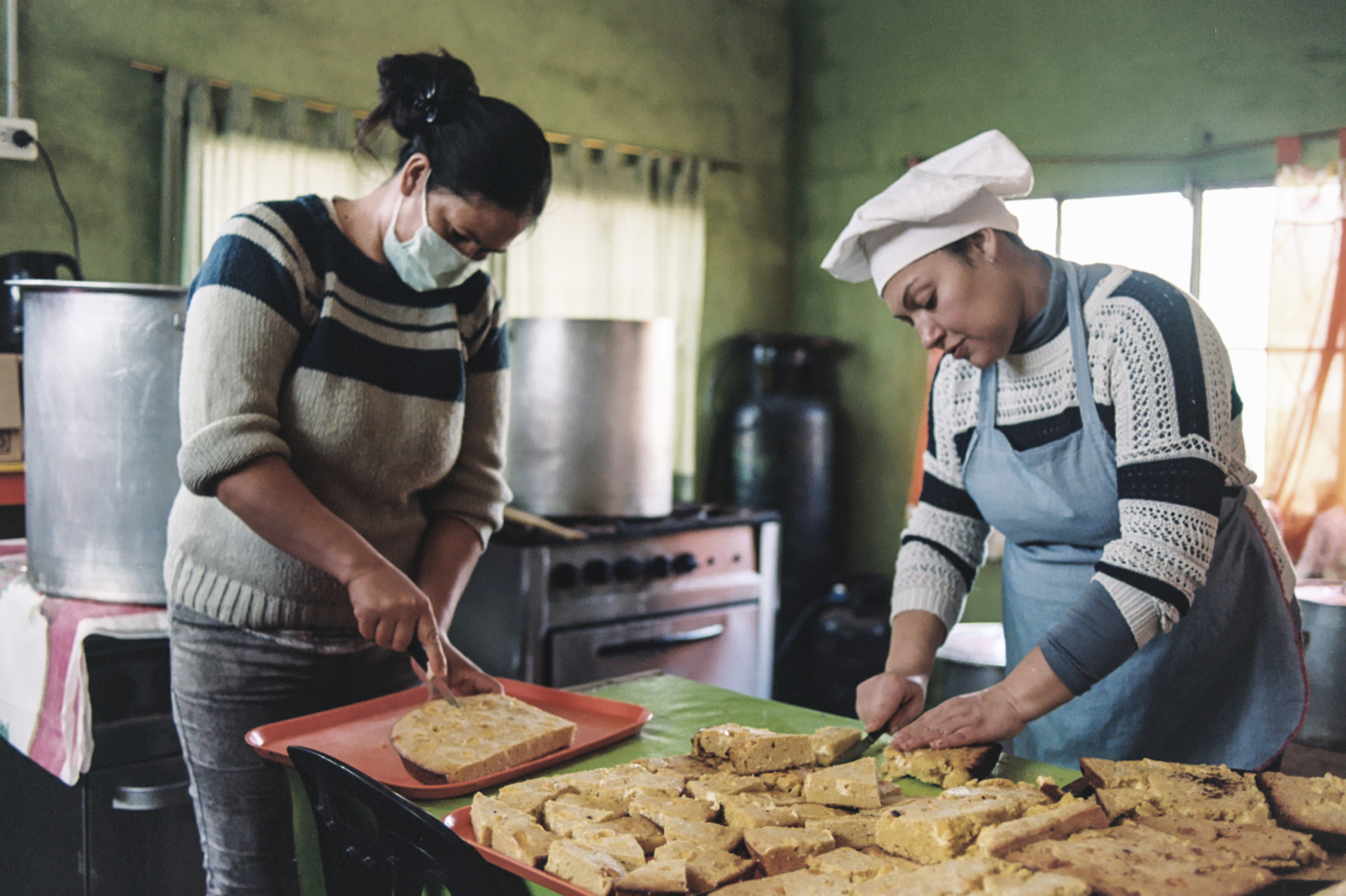 Sole and Moni, two migrant women from Paraguay, prepare a typical dish called 'sopa paraguaya' that will be distributed for their neighbors in the soup kitchen of the civil association Los Amigos of Barrio Sarmiento, Villa Ballester, San Martín, Buenos Aires, Argentina, July 24th, 2020. My name is Analía Cid (@analia.cid) and I'm a documentary photography, sociologist and feminist activist from Buenos Aires, Argentina. I currently work as a primary health care worker and the last year I decided to document the experiences my coworkers and I have gone through because of the coronavirus pandemic.analiagcid@gmail.com, 04. Analia Cid - Analia-Cid-Contact_01